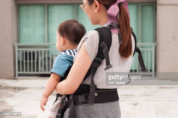 A young mother is carrying her baby boy on a baby carrier