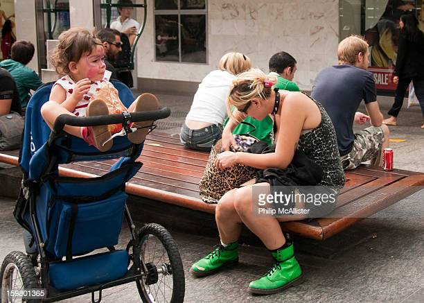Young mother is dressed punk style with studded dog collar and leopard print top.She is searching in a plastic leopard print bag.Her baby has a...