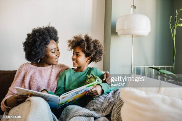 young mother is reading a book to her daughter - family with one child stock pictures, royalty-free photos & images