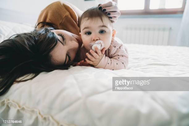 jovem mãe beijando sua filhinha - bico - fotografias e filmes do acervo