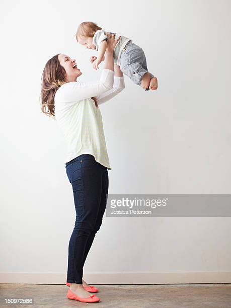 Young mother lifting baby boy (6-11 months) mid-air
