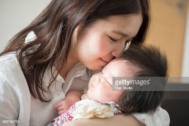 愛する若い母親 彼女のベビーガールご自宅で