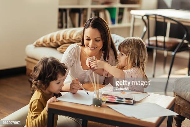 Young mother painting with kids