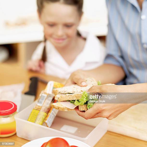 Young mother placing a ham sandwich into a lunch box with a young girl (8-10) watching her