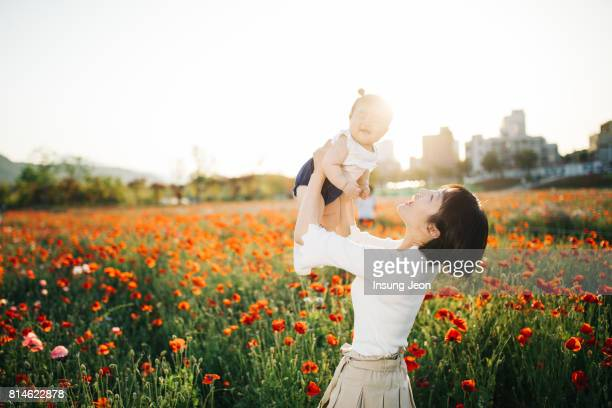 Young mother playing with her baby girl in a park
