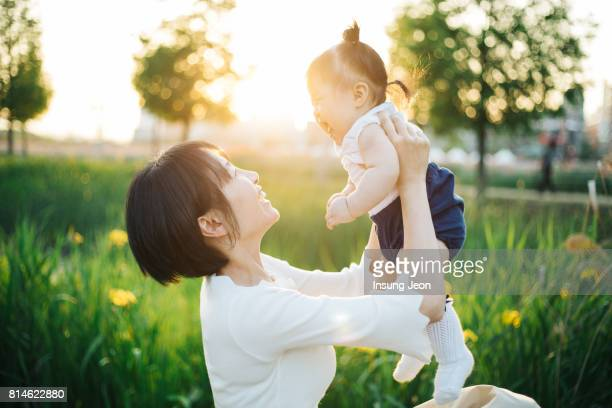 young mother playing with her baby girl in a park - asian baby stockfoto's en -beelden