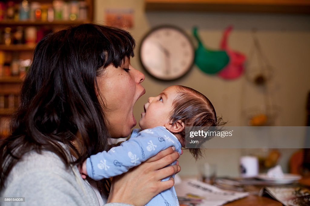 Young mother playing with her baby (2-5 months) in kitchen : Stock Photo