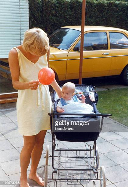Young mother playing with her baby in pram