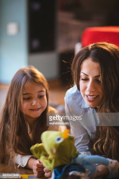 young mother playing with her daughter and a puppet - puppet stock pictures, royalty-free photos & images