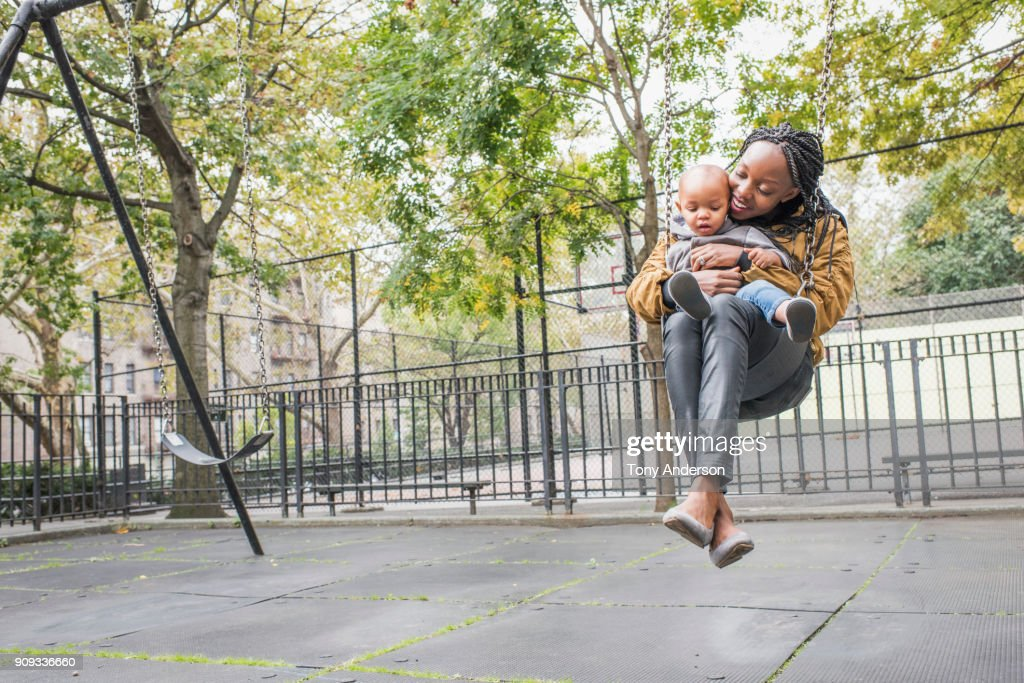 Young mother playing with infant daughter in city park : ストックフォト