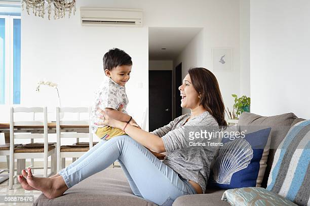 Young mother playing with toddler on her lap at home