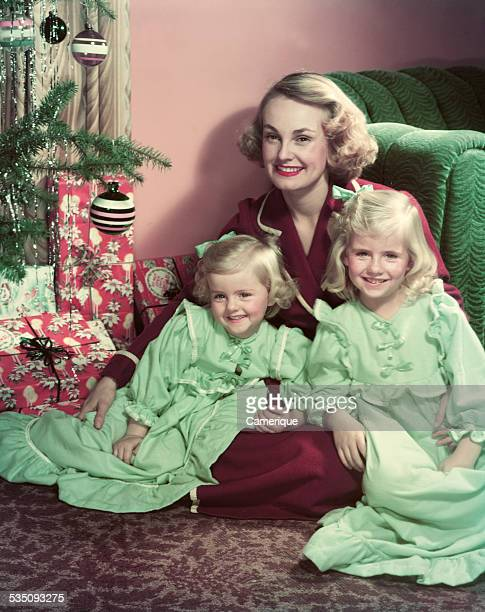 Young mother posed sitting on the floor with her 2 girls in front of a christmas tree Los Angeles California 1950s