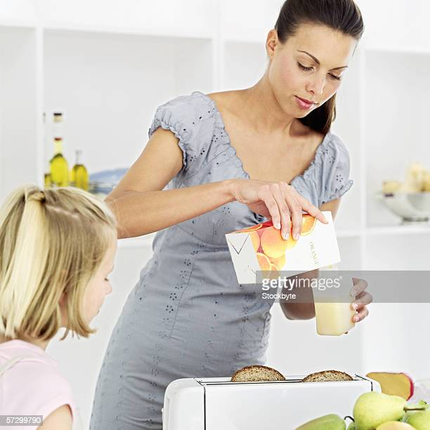 Young mother pouring out orange juice from a container into a glass with a young girl (13-14) watching