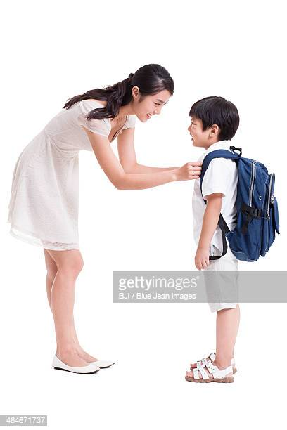 Young mother preparing son for school