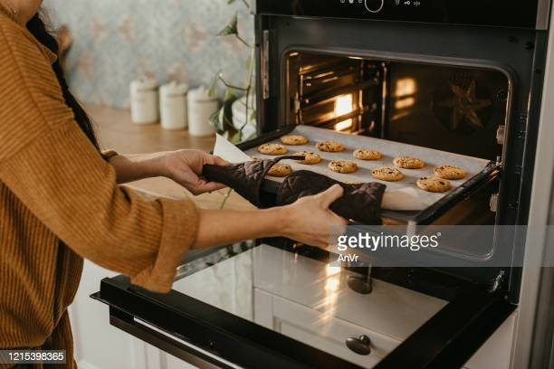 young mother putting a tray full of cookies in the oven - oven stock pictures, royalty-free photos & images