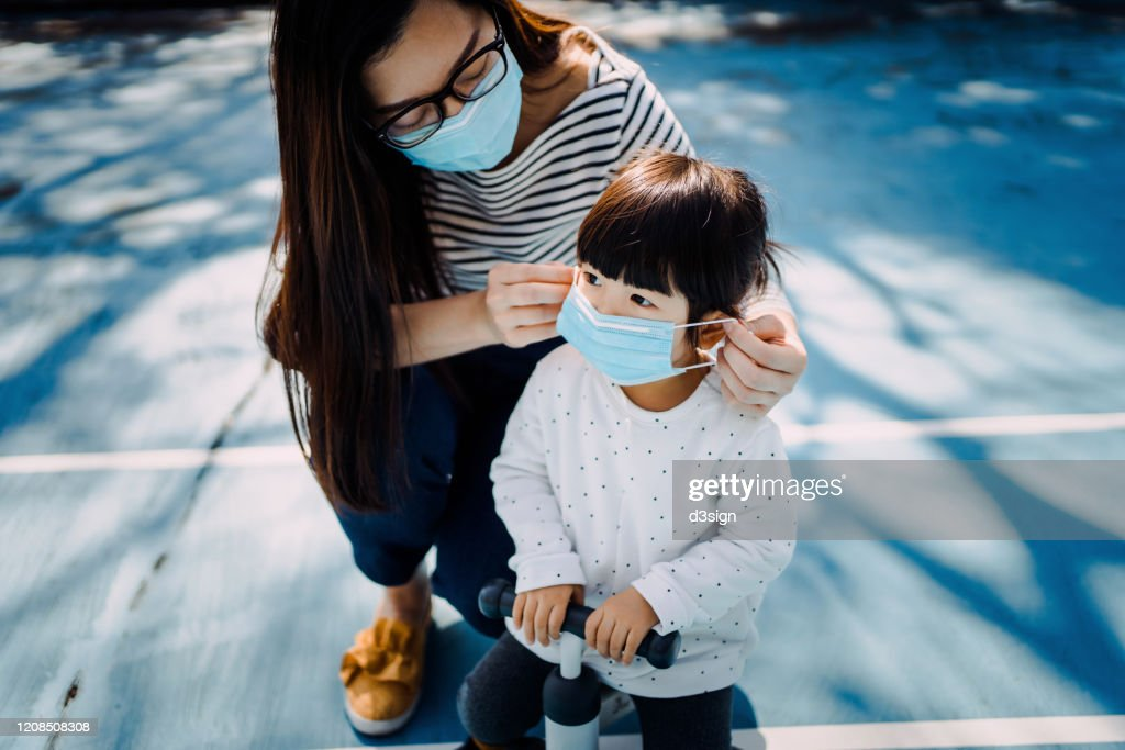 Young mother putting on surgical mask for little daughter in the playground to prevent the spread of cold and flu and viruses : Stock Photo