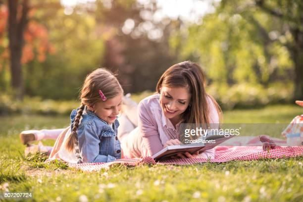 Young mother reading a book to her small girl on a picnic.