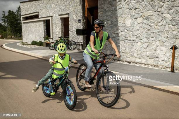 young mother riding bike with her son - helmet stock pictures, royalty-free photos & images