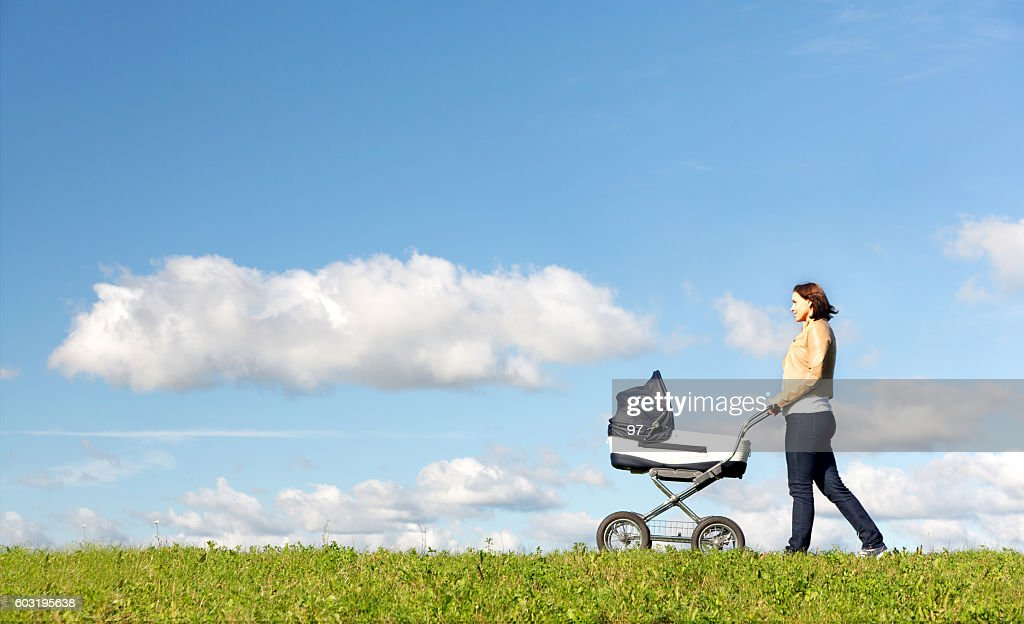 Young mother running while pushing a stroller on meadow : Stock Photo