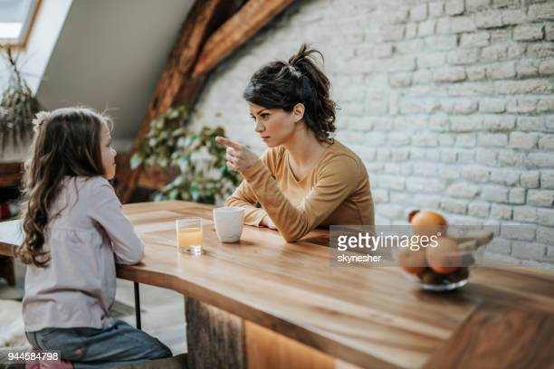 young mother scolding her little daughter at home. - mother scolding stock pictures, royalty-free photos & images