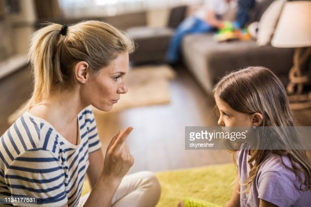 young mother scolding little daughter in the living room. - mother scolding stock pictures, royalty-free photos & images