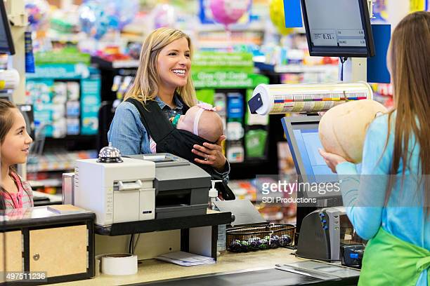 Young mother shopping at grocery store with daughters