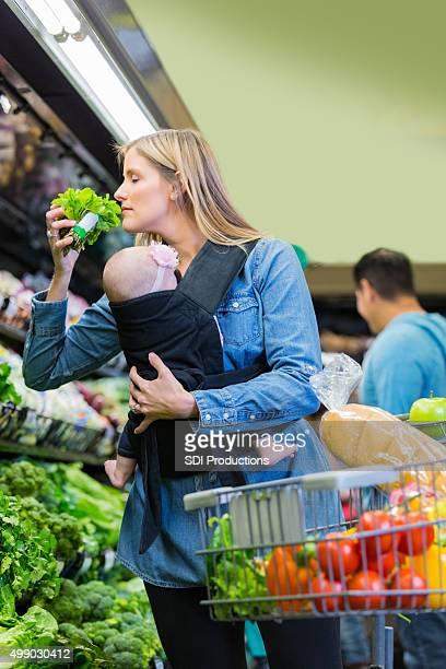 Junge Mutter Einkaufen für gesunde Lebensmittel im Supermarkt mit Kleinkind