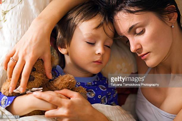 Young mother, sleeping with her baby boy