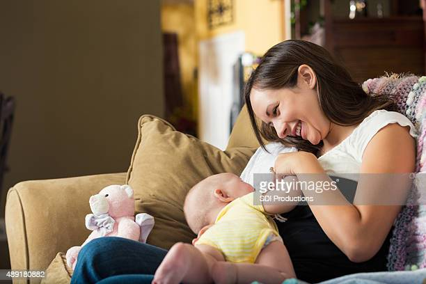 young mother smiling while breastfeeding daughter at home - breastfeeding stock pictures, royalty-free photos & images