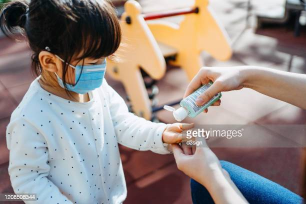 young mother squeezing hand sanitizer onto little daughter's hand in the playground to prevent the spread of viruses - coronavirus foto e immagini stock