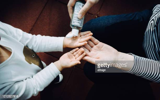 young mother squeezing hand sanitizer onto little daughter's hand in the playground to prevent the spread of viruses - antiseptic stock pictures, royalty-free photos & images
