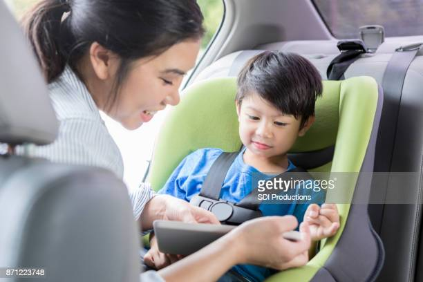 Young mother starts digital tablet for son before car trip