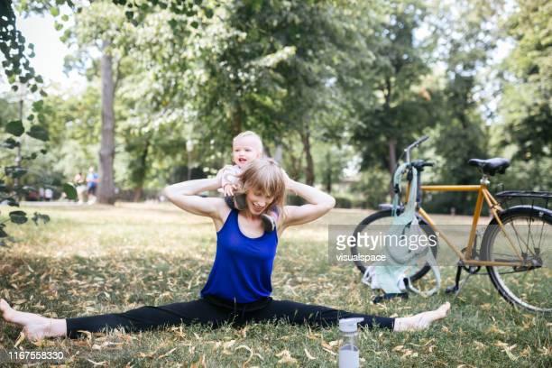 若い母親は、公共の公園で彼女の赤ちゃんを楽しみながらストレッチ - プレンツラウアーベルグ ストックフォトと画像