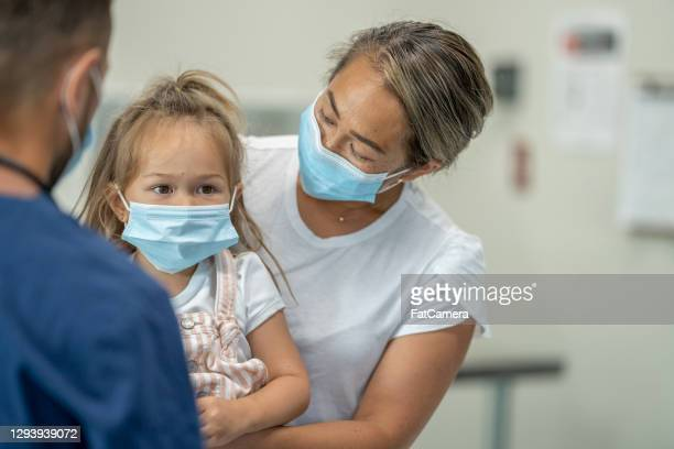 young mother takes her daughter for a doctor's visit - fatcamera stock pictures, royalty-free photos & images