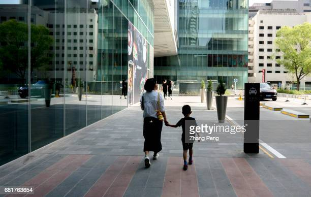 Young mother takes her only kid walking on the street Since October of 2015 China's full implementation of the two child policy the government had...