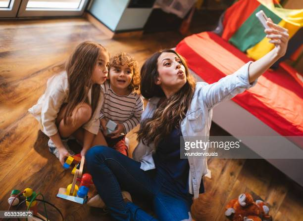 Young mother taking a selfie with her son and daughter