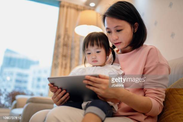 Young mother teaching her daughter with a digital tablet