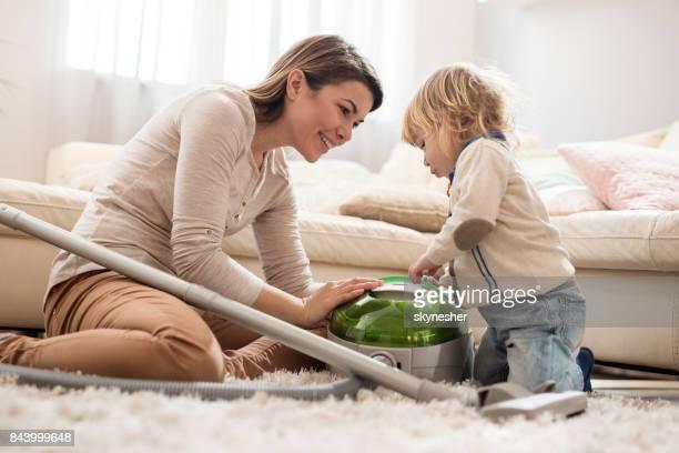 Ung mamma lär hennes små son hur man använder dammsugare hemma.