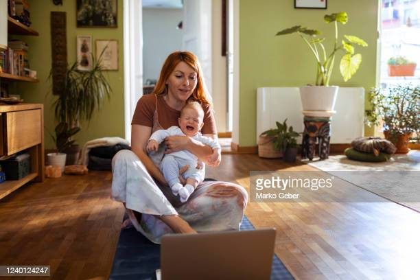young mother using a laptop with her daughter - mindzoom 2 stock pictures, royalty-free photos & images