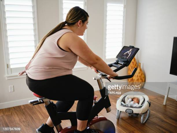 young mother using exercise bike in a home - chubby asian woman stock pictures, royalty-free photos & images