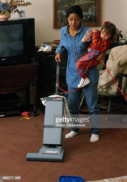 Young mother vacuuming while carrying daughter (1-2)