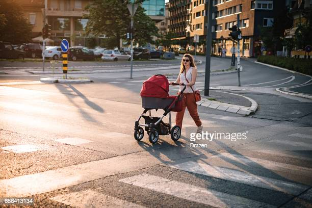 Young mother walking across the pedestrian crosswalk