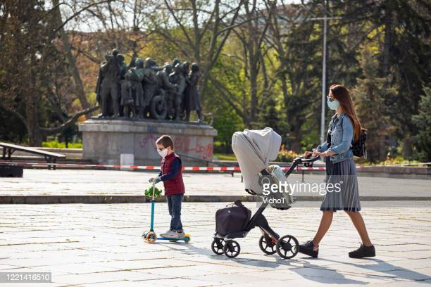 young mother walking with her children nearby restricted public park area due to pandemic - forbidden stock pictures, royalty-free photos & images