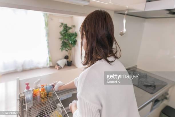若い母親は、台所で皿洗い