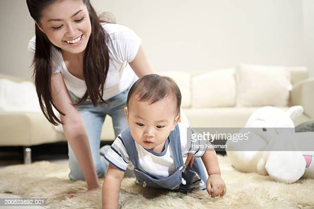 young mother watching baby boy (9-12 months) crawling in living room - 12 23 months stock pictures, royalty-free photos & images