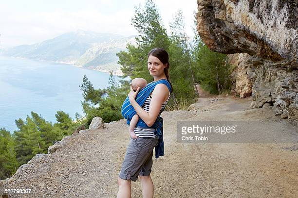 young mother wearing baby in wrap on a hike - kangourou photos et images de collection