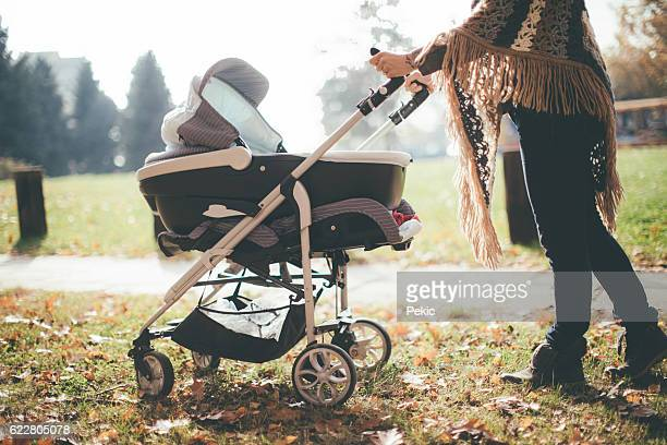 young mother with a baby stroller - pushchair stock pictures, royalty-free photos & images