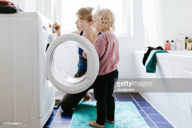 young mother with a child washing clothes together - laundry stock pictures, royalty-free photos & images