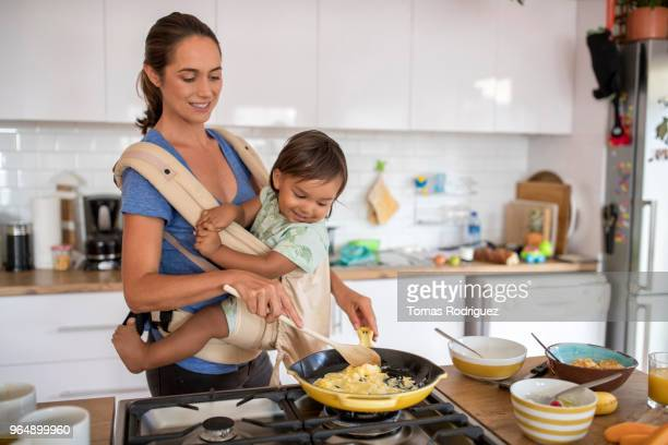 Young mother with a toddler in a baby carrier cooking food