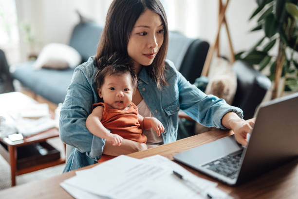 Young mother with baby daughter working from home